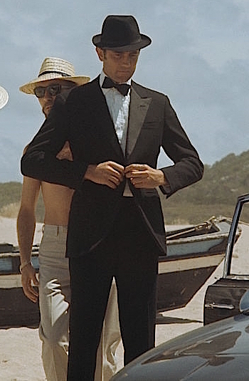 George Lazenby in costume and on location as James Bond beside his Aston Martin DBS in On Her Majesty's Secret Service (1969)
