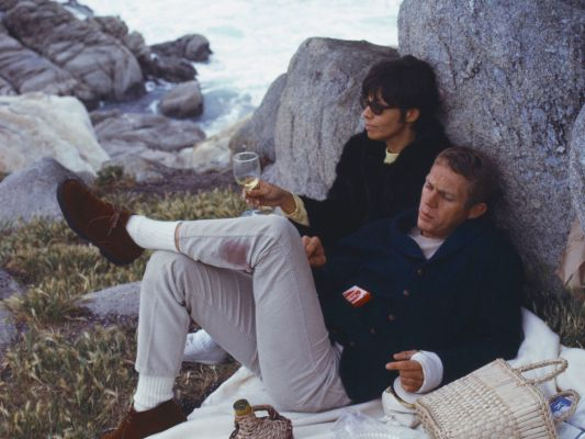 McQueen kicks back with Neile at Carmel. Note the wine-stain on his pants, and imagine just how carefree the couple felt in that moment. (Photograph by William Claxton, 1964)