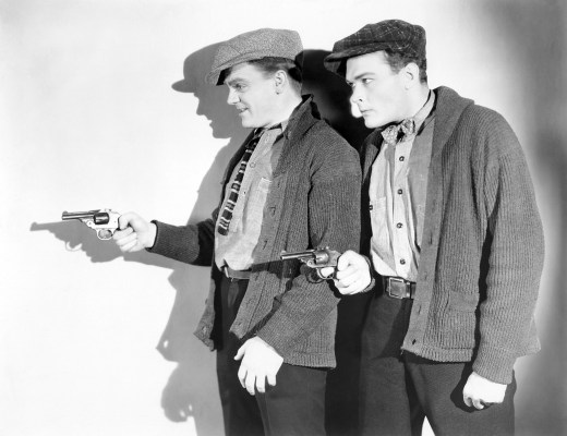 Publicity photo of James Cagney and Edward Woods in The Public Enemy. While the costumes match those worn on screen, their Colt Police Positive revolvers have been replaced here with smaller break-top revolvers.