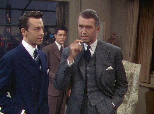 "Rupert's gray tweed suit bridges the gap between the cool, calculating Brandon in navy serge and the anxious, earthier Phillip in his brown striped suit. While gray can have businesslike connotations, the tweed suiting brings Rupert's ensemble ""down to earth"" and subconsciously presents his morality more in line with the less murderous Phillip."