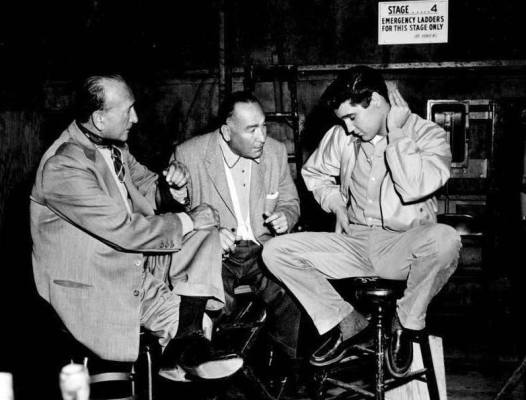 Producer Hal B. Wallis sits with director Michael Curtiz and star Elvis Presley on the set of King Creole (1958).
