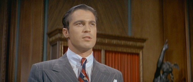 McGurn's constricted pinned collar and narrow tie knot counter his wide lapels that flank a half-foot in each direction.