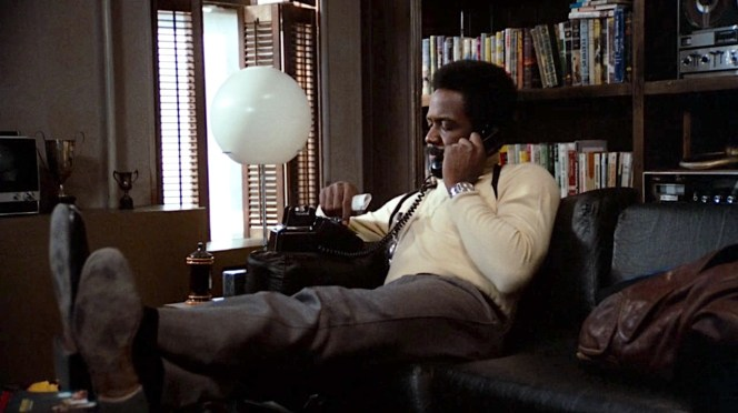 Note Shaft's brown leather trench coat next to him on the sofa.