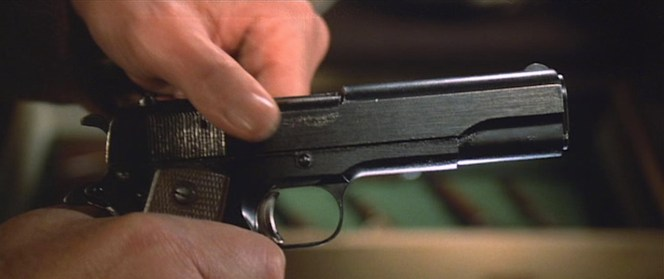 Harry pulls back the slide of his .45. Note the scratched-off serial number just below the ejection port.