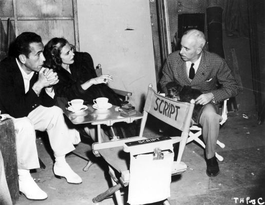 Humphrey Bogart and co-star Dolores Moran on set with director Howard Hawks. Bogie's scenes with Moran were significantly cut down from the original script to avoid taking away from his on-screen chemistry with Lauren Bacall, despite Hawks' disapproval of their off-screen romance.