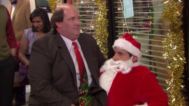 As Kevin mulls over what to ask Santa, episode writer Mindy Kaling can be seen laughing over Brian Baumgartner's shoulder. Kaling also wrote, produced, and directed episodes for the series.