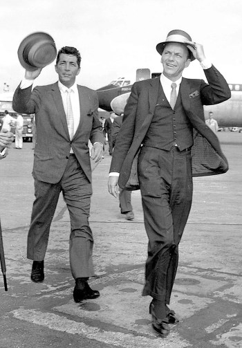 Frank Sinatra leads fellow Rat Packer Dean Martin across the tarmac as they greet fans at Heathrow Airport, August 1961.
