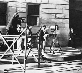 On the set of The Public Enemy, a gunman aims a Thompson submachine gun loaded with live ammunition at the wall next to James Cagney.