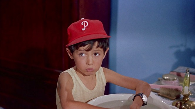 Nando sports Mike's gifts to encourage Americanization: a Phillies cap and an alarm watch.
