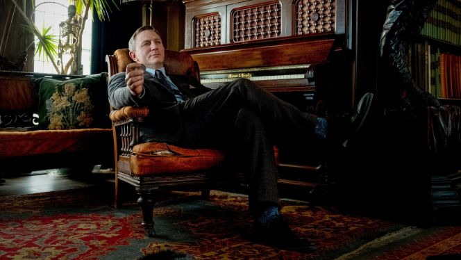 Blue is Benoit Blanc's color of choice for his introductory scene, coordinating his shirt, tie, and socks with Daniel Craig's bright blue eyes.
