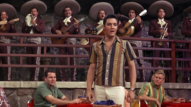 Elvis shows the crowd at La Perla how to stylishly wear a bold-striped shirt, while the patron to the King's left jealously seethes in his Fruit Stripe gum-inspired button-down.