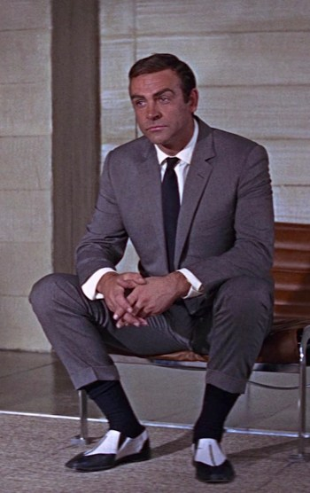 Sean Connery as James Bond in You Only Live Twice (1967) wearing a tasteful gray herringbone suit and, um, improvised footwear solutions.