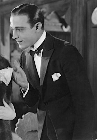 Rudolph Valentino, one of the most fashionable matinee idols of the era, wears a peak-lapel dinner jacket, wing collar, and white pocket square in the silent romantic drama Beyond the Rocks, released in May 1922, just months before the setting of The Great Gatsby.