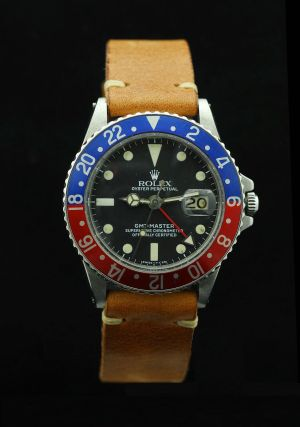 """Rolex GMT Master with a """"Pepsi"""" bezel and leather strap, similar to Ransom's watch in Knives Out."""