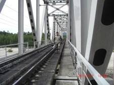 Kev walking a railway bridge.