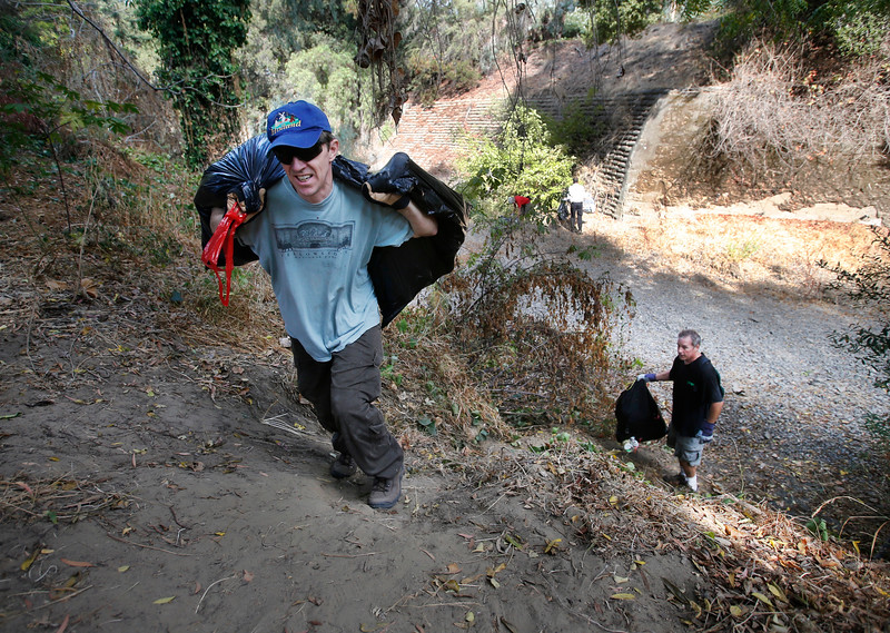Hamilton Hitchings, left, of Palo Alto, and Peter Drekmeier, of Palo Alto, haul trash bags as volunteers gather to conduct a cleanup of the shores along San Francisquito Creek in Menlo Park, Calif., Sept. 20, 2014.  (Patrick Tehan/Bay Area News Group)