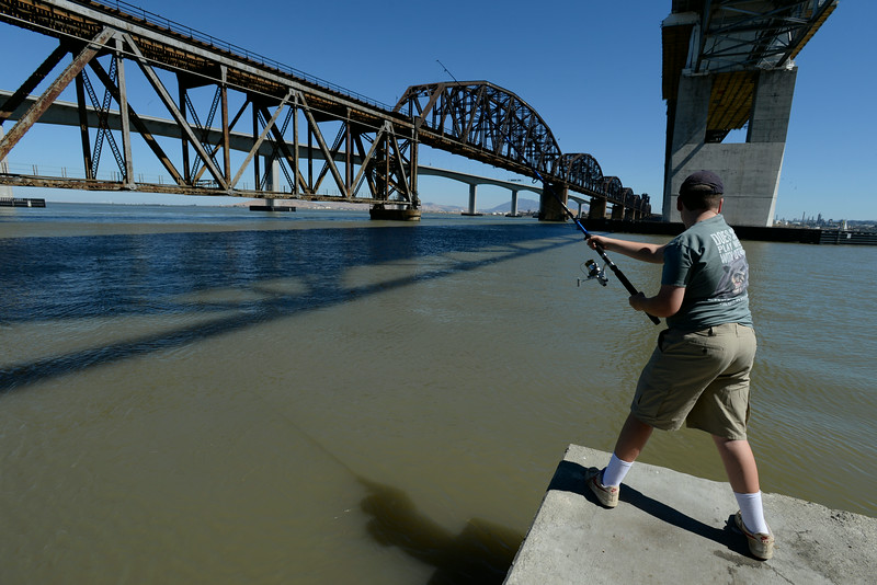 Michael Upton, 13, of Benicia, fishes from underneath the Benicia-Martinez bridge while the Benicia-Martinez Railroad Drawbridge can be seen in the background in Benicia, Calif., on Friday, Aug. 15, 2014. (Jose Carlos Fajardo/Bay Area News Group)
