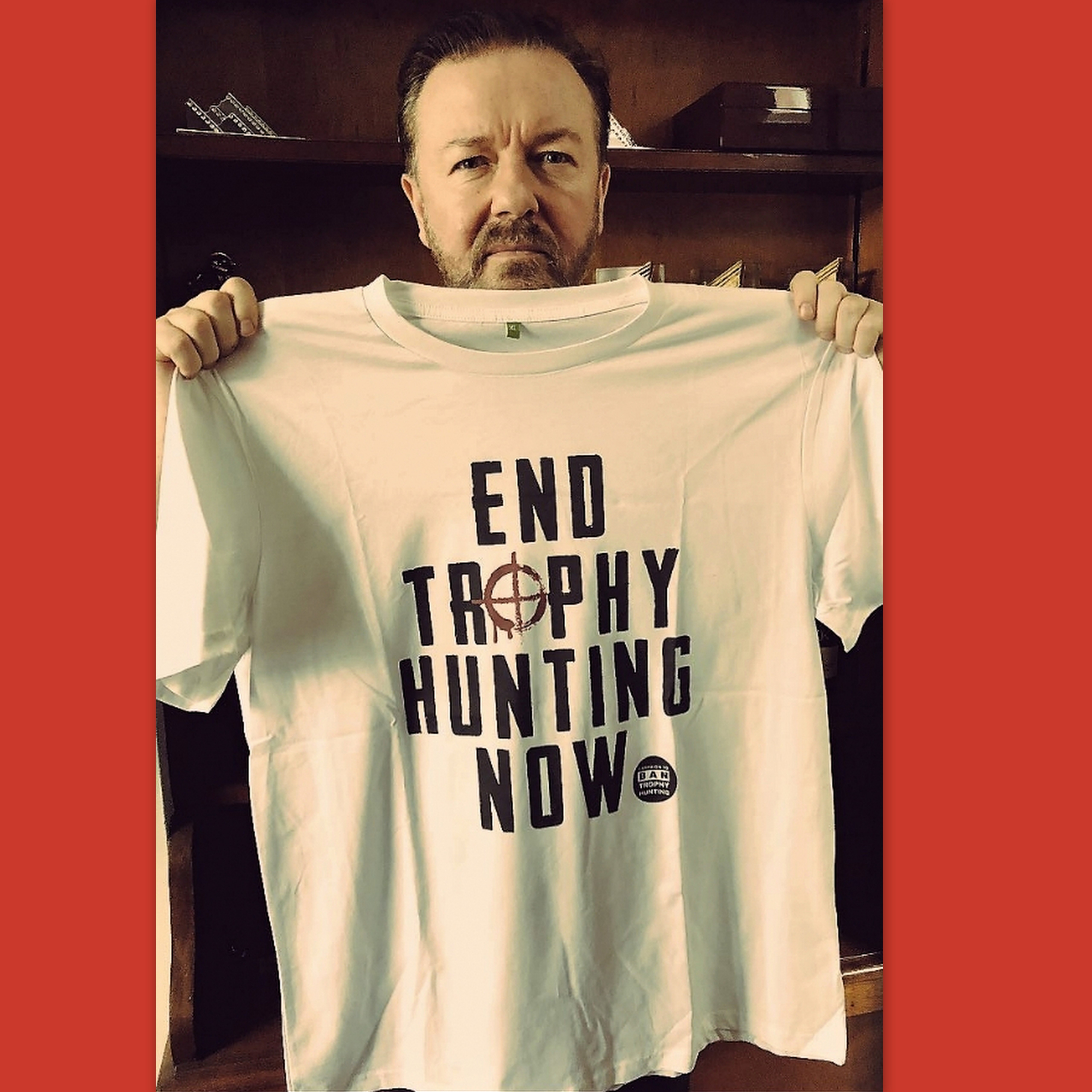 Ricky Gervais holds up our slogan Tee