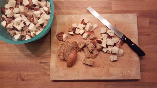 Das Brot in Würfel schneiden