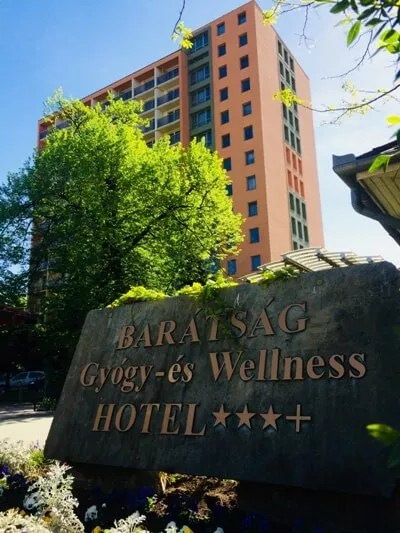 Hotel cégtábla háttérben az épülettel