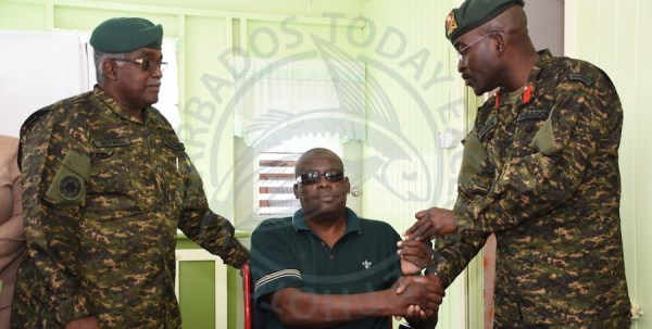 Barbados Defence Force chief of staff Glyne Grannum (right) hands over the keys to the renovated home to Eutice Forde while Major Lubin Maxwell (left) looks on.