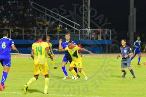 Bajan Tridents' goal-scorer Hallam Hope challenging his former Bury Football Club teammate and one of Guyana's goal scorers, Neil Danns.