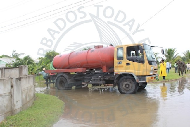At Wotton: A tanker from the Ministry of Transport, Works and Maintenance pumps off the flood waters.
