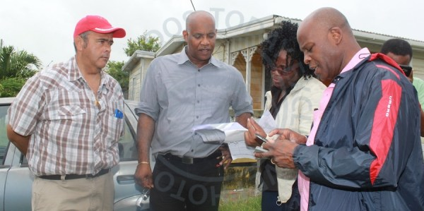 From left, Cabinet Ministers Dr William Duguid, Dale Marshall and Edmund Hinkson (right), exchanging notes with Director of Emergency Services Kerry Hinds (second from right).