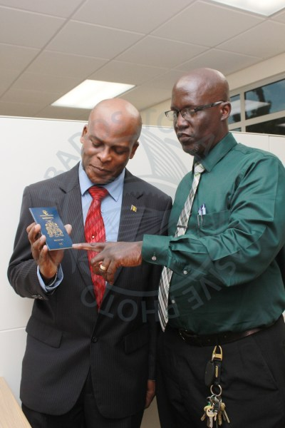 Minister of Home Affairs Edmund Hinkson and Chief Immigration Officer Wayne Marshall, showing one of the new e-passports, which are biometrically enabled with a chip and antenna in the cover which increases the security features.