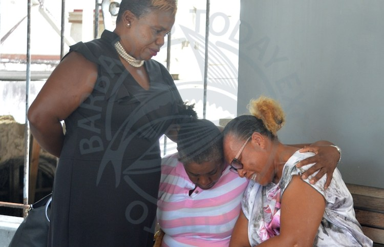 Stephen 'Molly' Small's sisters (sitting) Slyvia and Joyce Small cried openly today as the two people accused of murdering him appeared in the District 'A' Magistrate's Court.