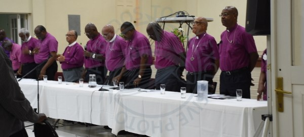Members of the House of Bishops stand for the closing prayers offered by Bishop Errol Brooks (fifth from left), while next to him on the left is former Anglican Bishop of Barbados Drexel Gomez, who assumed his post under similar circumstances in 1972.