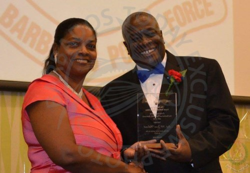 From left, The late Juan Walrond receiving a service award from Chief Justice Sir Marston Gibson in 2014.