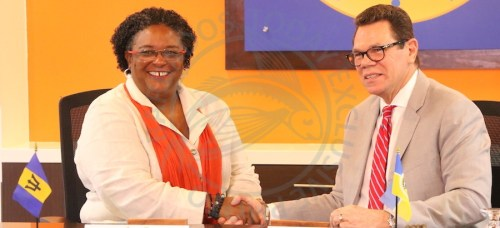 Prime Minister Mia Mottley (left) shakes hands with CDB President Dr Warren Smith after today's signing.