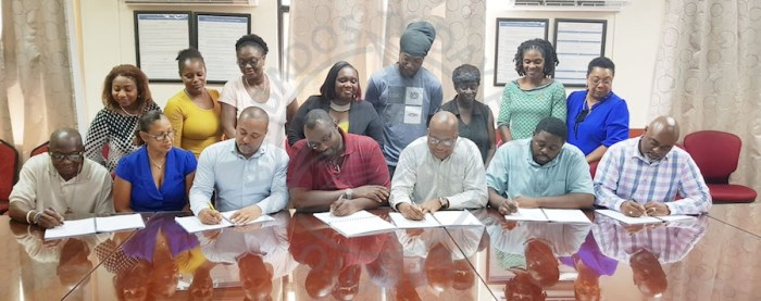 Seated: BHTA's Chairman Stephen Austin and BWU's Dwaine Paul (third and fourth from left respectively) at the signing of a three-year Collective Agreement for tourism industry workers recently, with other BHTA and BWU representatives including BHTA's Senator Rudy Grant (right), Jerry Lewis (third from right) and Gail Springer (second from left), as well as BWU's Stephen Williams (left) and Cameron Layne (second from right) look on.