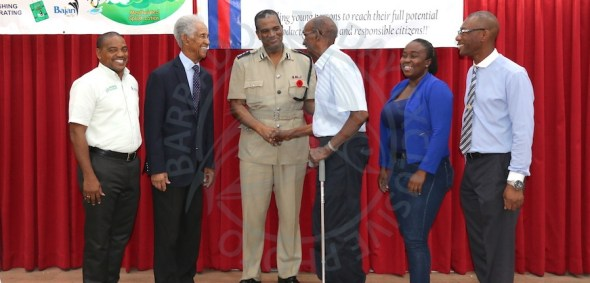 Police Boys & Girls Club stalwart Adrian Garnes (third right) greeting acting Commissioner of Police Erwin Boyce while looking on are (l-r) Armstrong Agencies' Ortis Williams, Sir Garfield Sobers, Veronica Carrington and Inspector Fred Clarke.