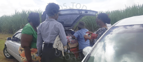 Teachers purchasing food from a vendor outside the school gate.