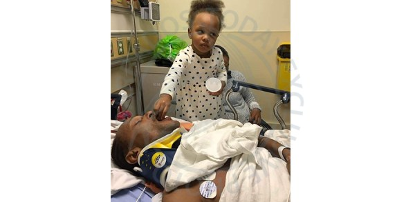 An incapacitated Patrick Husbands being fed ice by his three-year-old daughter Charity Husbands at the Sunnybrook Hospital.