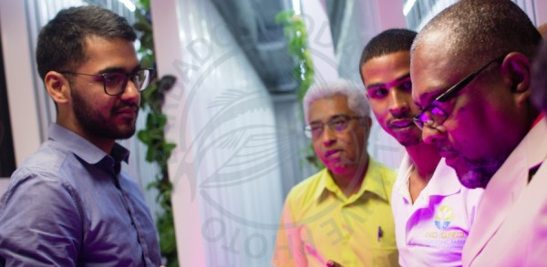 Minister Indar Weir (left) under the artificial sunlight provided by the agricultural farm, being schooled by Ino Gro co-directors Rishi Pajwani (left) and Warren Kellman (second from right) as mentor Ayub Kola looks on.