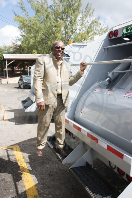 Minister of Environment and National Beautification Trevor Prescod hops on one of the two new garbage trucks that will be servicing communities in St Michael.