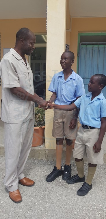 Reynold Weekes Principal Anderson Bishop (left), congratulating students Jaquon Blackman and Jerome Forde (right) for their role in returning a lost wallet to its owner.