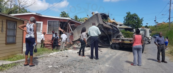 The scene at Dunscombe St Thomas where a tractor crashed into a house after it fell off a trailer truck.