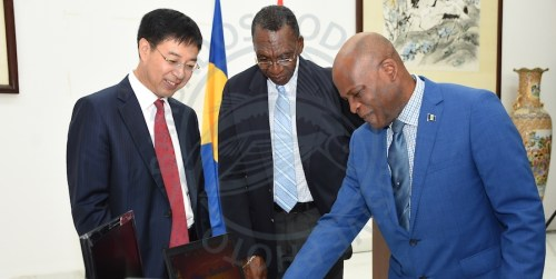 Minister of Home Affairs Edmund Hinkson (right), going through the features of one of the laptops donated to Barbados by the Chinese government, as Chinese Ambassador Yan Xiusheng (left), and Principal of the Government Industrial School Erwin Leacock look on.
