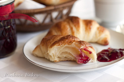 Croissants on a white plate with blackberry jam