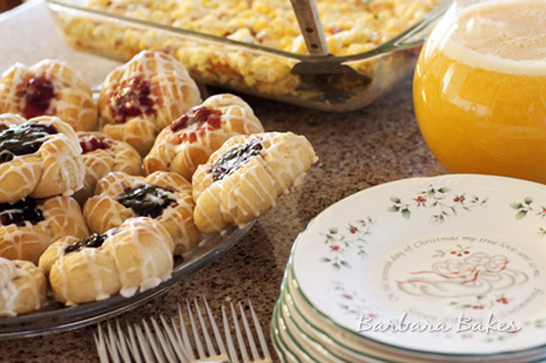 Blackberry and Cherry Kolaches with a large glass of Orange Juice and a large egg casserole in background