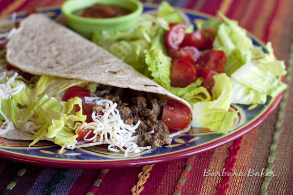 ground beef taco on a plate with a salad and salsa