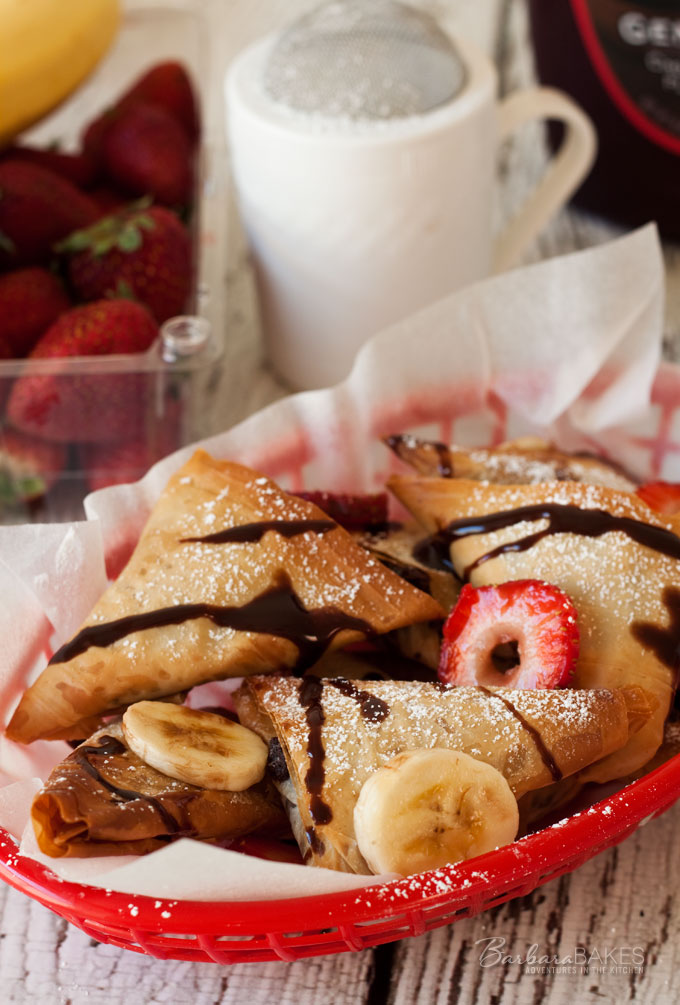 Baked Nutella turnovers - phyllo dough wrapped around a sweet, creamy, chocolaty Nutella cream cheese filling baked until it\'s crispy, flaky, and golden brown then served with sliced strawberries and bananas, drizzled with chocolate and sprinkled with powdered sugar.