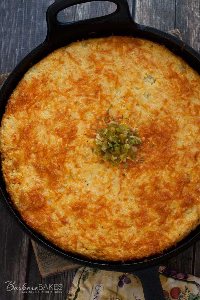 Cheesy Green Chile Cornbread baked in a hot cast iron skillet.