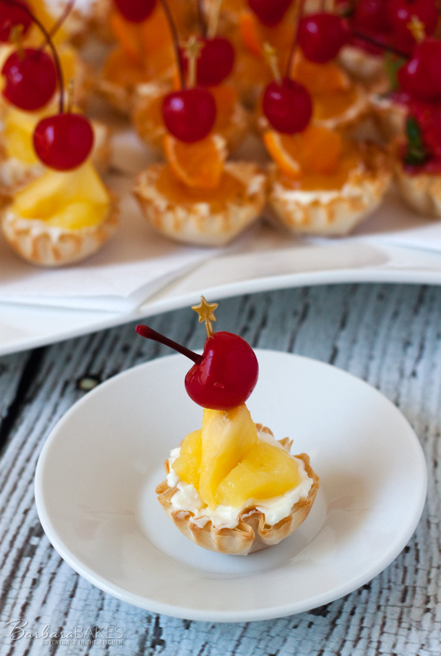 Creamy no-bake coconut cheesecake in a crisp, flaky mini fillo shell topped with a sweet pineapple topping and garnished with fresh pineapple and a maraschino cherry.