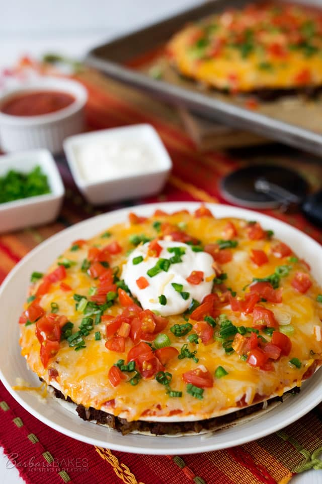 A fun Mexican Pizza with a layer of refried beans and spicy ground beef sandwiched between two flour tortillas, topped with salsa, shredded cheese, jalapenos, green onions, and tomatoes. Then baked until it\'s hot, melty and gooey delicious.