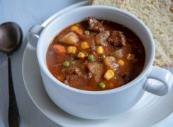 Round steak beef stew with colorful vegetables in a white bowl